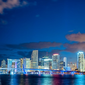 Miami, flórida, pôr do sol com edifícios residenciais e comerciais iluminados e uma ponte na baía de biscayne