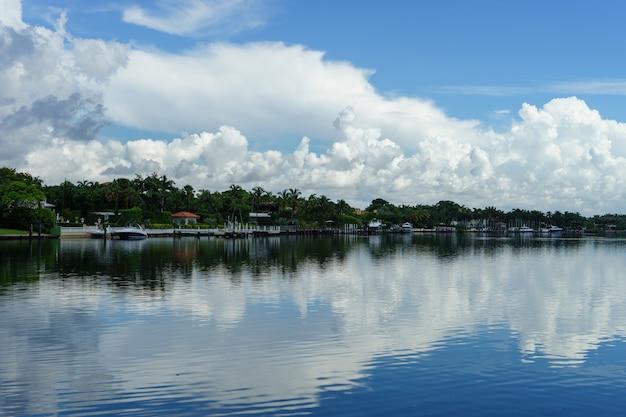 Miami. praia do sul. vista de belas casas do outro lado do rio com belas nuvens e reflexo na água