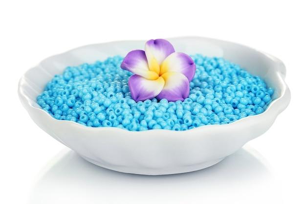 Miçangas coloridas com flor artesanal em prato isolado no branco
