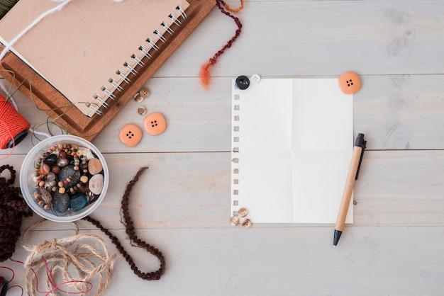 Miçangas; cordas e botões e caneta em papel branco sobre o pano de fundo de madeira