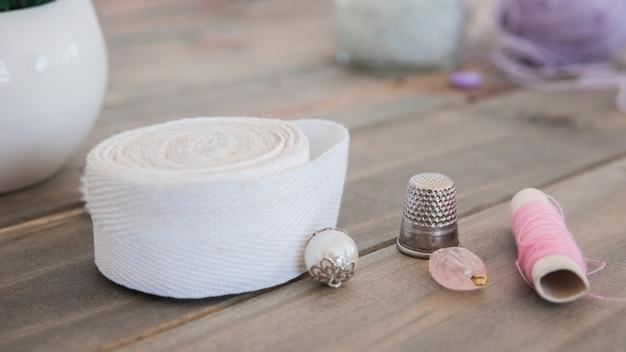 Miçangas; dedal; fita branca e carretel rosa na mesa de madeira