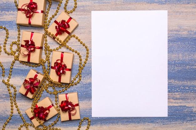 Miçangas douradas, presentes embrulhados em papel kraft com um laço vermelho e papel em branco sobre um fundo de madeira. árvore escaldada, arranhões azuis. conceito de flat lay
