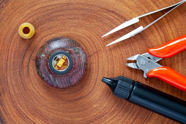 Micro bobina única com algodão no atomizador de gotejamento reconstrutível em suporte de madeira estabilizado com ponta de gotejamento ultem, pinça de cerâmica, alicate de corte