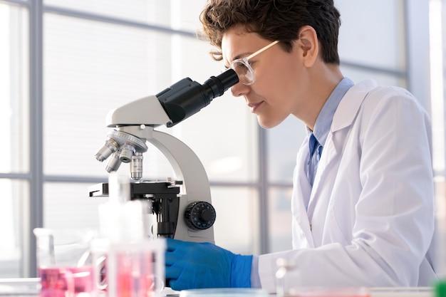 Microbiologista focado em óculos, sentado à mesa e usando microscópio para pesquisa em laboratório