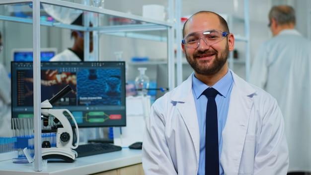 Microbiologista sentado no laboratório, olhando para a câmera em um moderno laboratório equipado. equipe multiétnica examinando a evolução do vírus usando ferramentas de alta tecnologia e química para pesquisa científica, desenvolvimento de vacinas