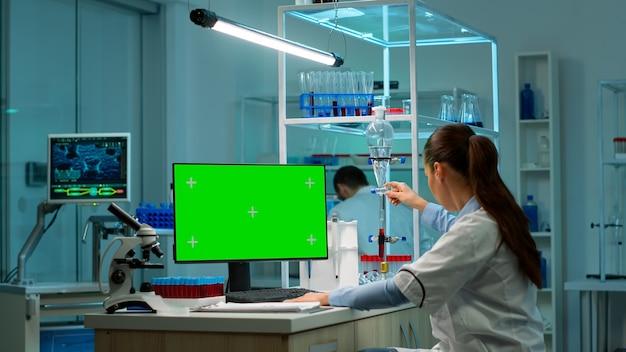 Microbiologista trabalhando no computador com visor, tela verde croma, conversando com um colega de trabalho sobre o novo vacutainer com amostras de sangue. equipe de cientistas de biotecnologia desenvolvendo drogas.