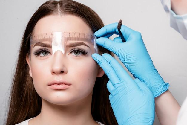 Microblading no salão de beleza. menina bonita sobre o procedimento cosmético para o tratamento de sobrancelhas. microprocessamento de sobrancelha.