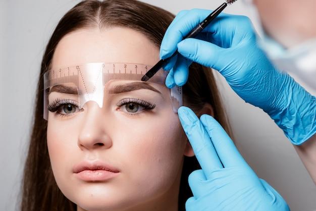 Microblading sobrancelhas fluxo de trabalho em um salão de beleza. mulher com as sobrancelhas coloridas.