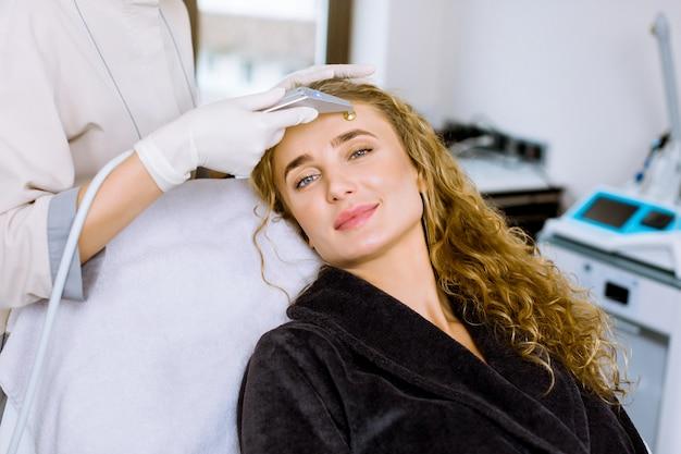 Microdermoabrasão de diamante, cosmético descascado na clínica moderna de cosmetologia. jovem mulher sorridente durante um tratamento de microdermoabrasão no salão de beleza