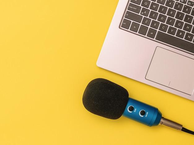 Microfone azul conectado a um computador laptop em um fundo amarelo. o conceito de organização do local de trabalho. equipamentos para gravação, comunicação e escuta musical.