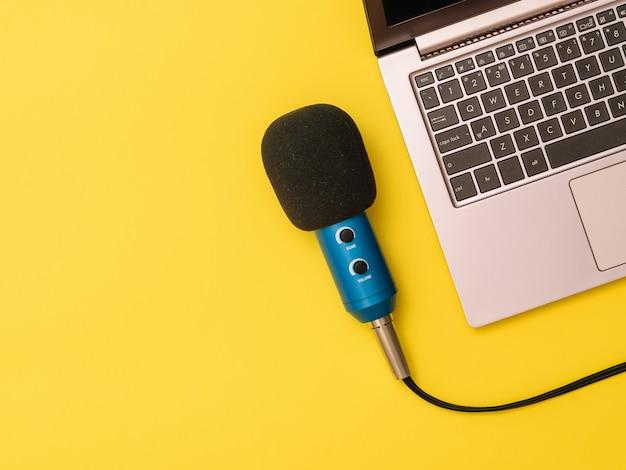 Microfone azul e um laptop na mesa amarela. o conceito de organização do local de trabalho. equipamentos para gravação, comunicação e escuta musical.