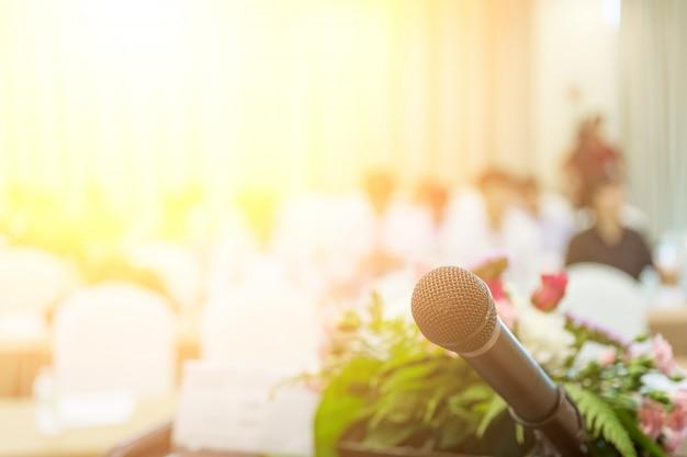 Microfone close-up tiro no seminário ou sala de reunião com as pessoas no foco do borrão para o espaço da cópia