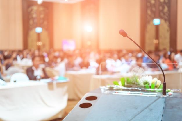 Microfone close-up tiro no seminário ou sala de reunião com as pessoas no foco do borrão