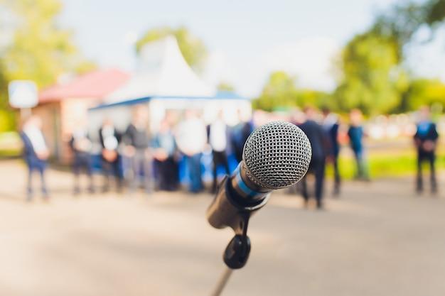 Microfone closeup no fundo desfocado com filtro de luz brilhante de filme de efeito, único microfone no parque e fundo desfocado.
