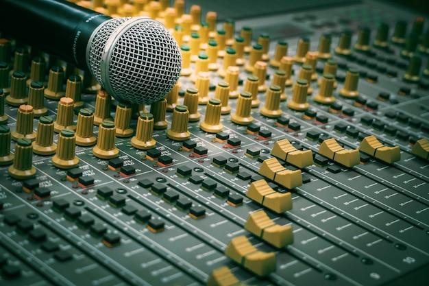 Microfone colocado junto com o mixer de áudio na sala de gravação