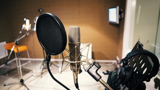 Microfone com filtro pop e anti-vibração de montagem contra choque e suporte de notas e tripé na produção de estúdio de partitura musical