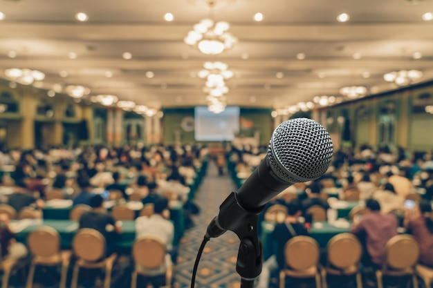 Microfone com foto desfocada abstrata da sala de conferências ou sala de reuniões com participante ba