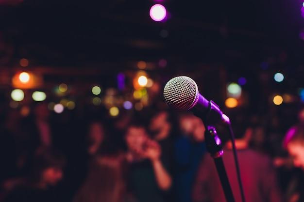 Microfone com luz brilhante colorida turva no fundo escuro da noite, imagem de foco suave para conceitos de comunicação de tecnologia de negócios.
