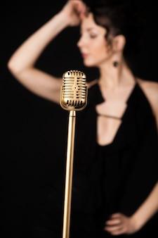 Microfone com mulher do borrão