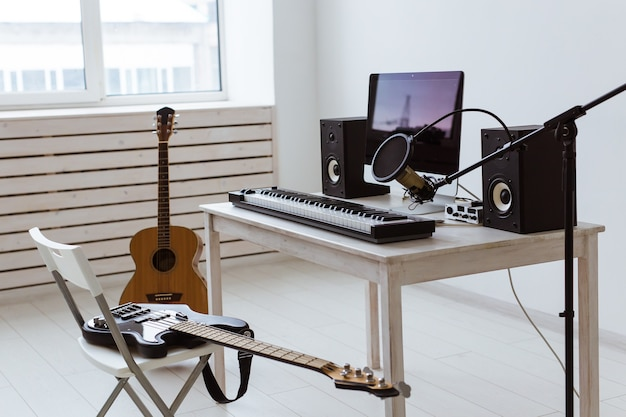 Microfone, computador e equipamento musical, guitarras e piano. conceito de estúdio de gravação em casa.