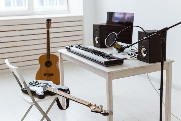 Microfone, computador e equipamento musical, guitarras e piano
