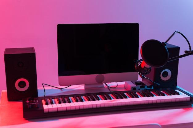 Microfone, computador e guitarras de equipamento musical e fundo de piano. estúdio de gravação caseiro