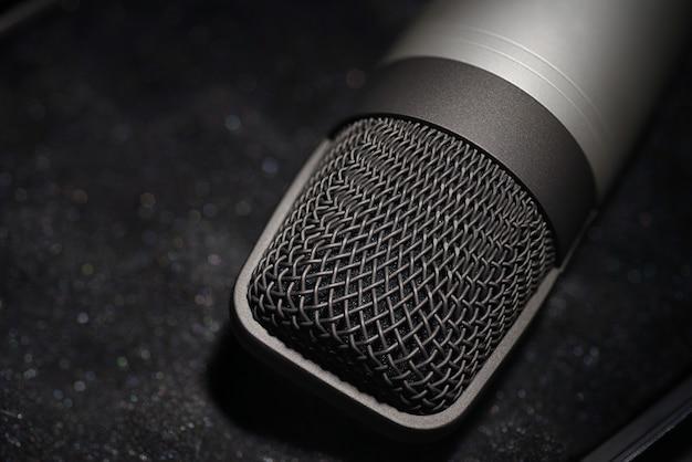 Microfone condensador de estúdio prateado em espuma macia preta com capa protetora