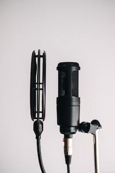 Microfone condensador preto em suporte com filtro pop