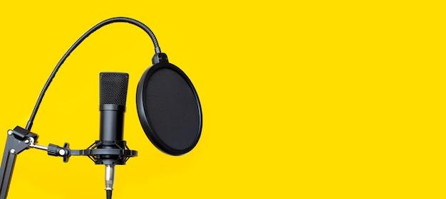 Microfone de estúdio em fundo amarelo.
