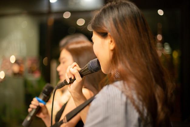 Microfone de foco selecionado e cantora irreconhecível no palco