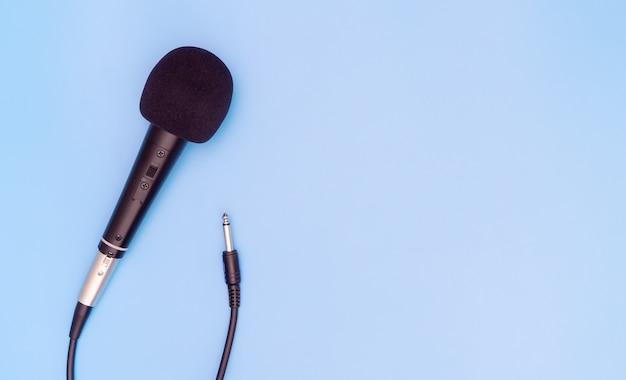 Microfone dinâmico preto no espaço da cópia azul