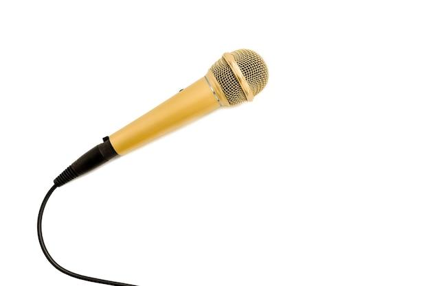 Microfone dourado com cabo em fundo branco.