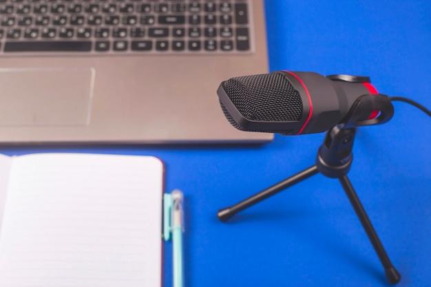 Microfone e bloco de notas para gravar podcast.