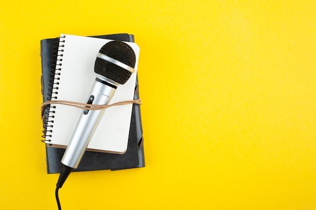 Microfone e caderno aberto vazio em papel amarelo