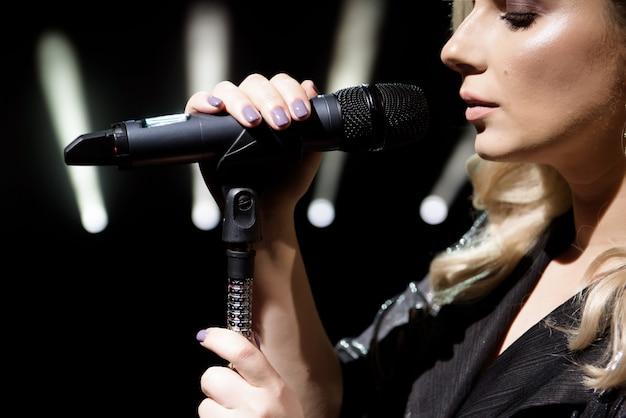 Microfone e cantor feminino close-up. mulher cantando em um microfone.