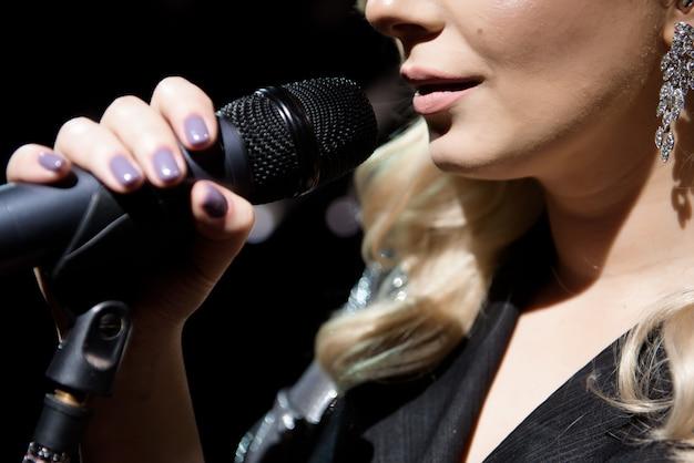 Microfone e cantora close-up. mulher cantando em um microfone.