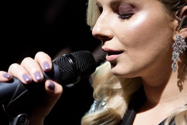 Microfone e cantora fecham. mulher cantando em um microfone, segurando o microfone com as duas mãos.