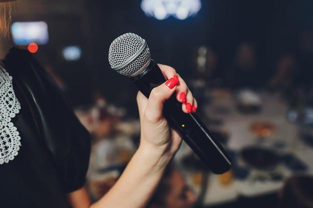 Microfone e cantora irreconhecível de perto