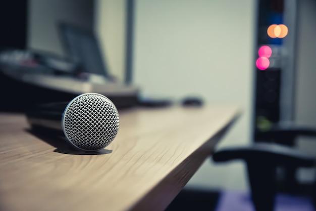 Microfone é colocado na mesa com laptop na sala de controle.