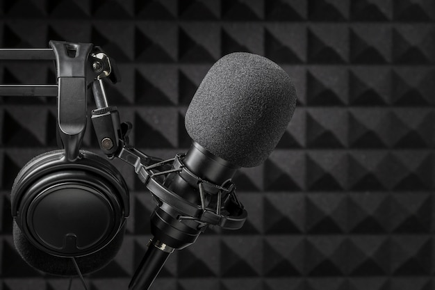 Microfone e fones de ouvido cercados por espuma de isolamento acústico