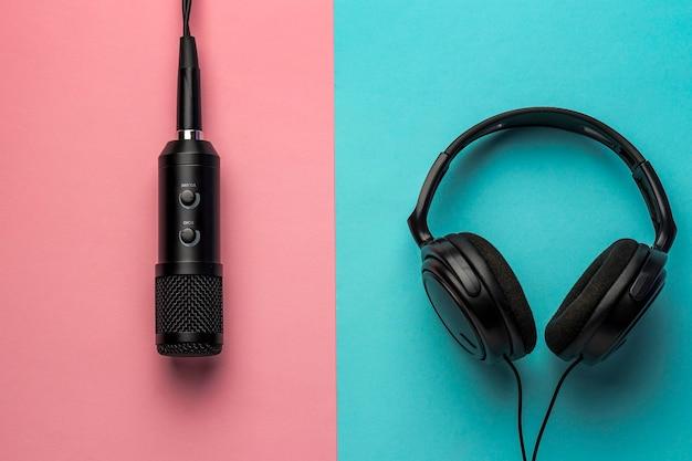 Microfone e fones de ouvido em fundo rosa e azul
