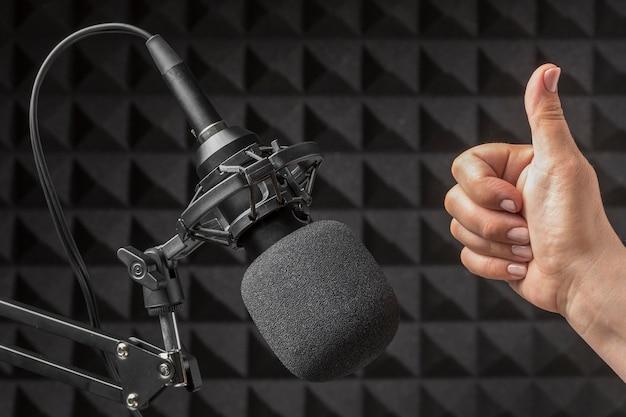 Microfone e mão rodeados por espuma de isolamento acústico