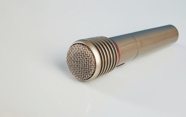 Microfone em close em uma mesa espelhada branca