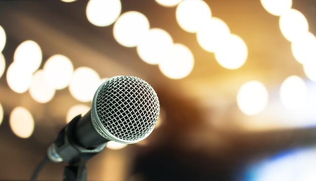 Microfone em resumo borrado de discurso na sala de seminários ou na sala de conferência, luz do auditório, concerto do evento bokeh background
