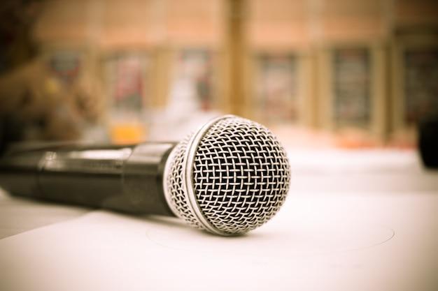 Microfone em resumo borrado do pódio dianteiro e discurso na sala de seminários