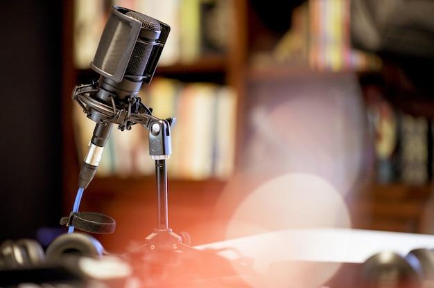 Microfone em um estúdio cercado por equipamentos sob as luzes com um fundo desfocado