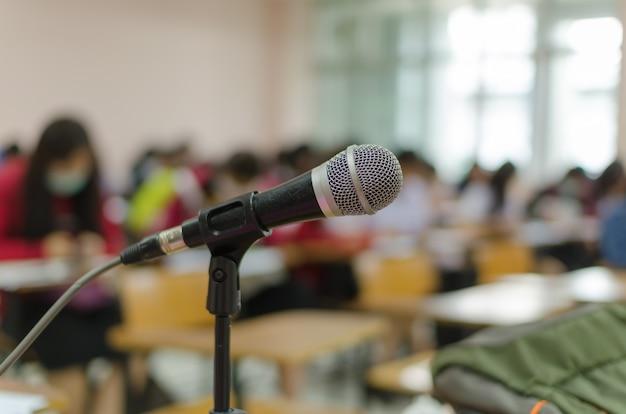 Microfone em um tripé em frente à sala de aula com fundo desfocado de estudantes fazendo