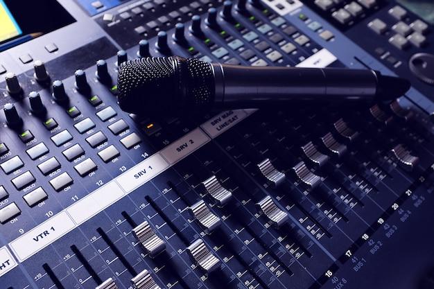 Microfone, equipamento de amplificação, botões de mixer de áudio de estúdio e faders. equipamento de engenheiro de som. mistura acústica de música, foco seletivo. a foto é coberta de areia e barulho.