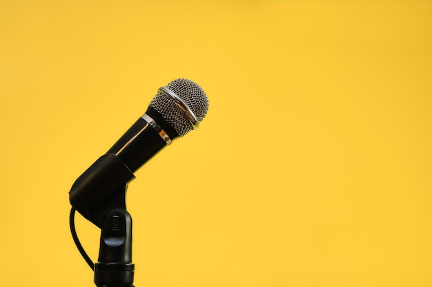Microfone isolado em fundo amarelo, conceito de comunicação.