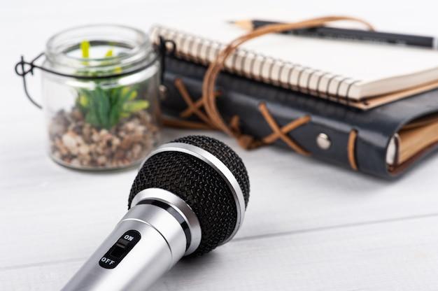 Microfone ligado, caderno em madeira branca